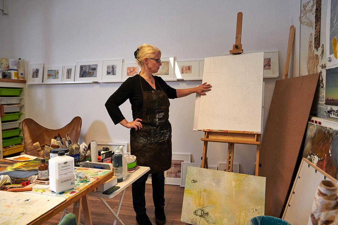 kunstreiche Ateliergefluester Künstlerin im Atelier vor weißer Leinwand